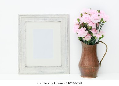 A white wood frame on a white background with a copper vase filled with miniature pink carnations.  A blank frame for display.
