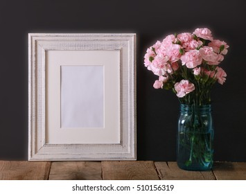 A white wood frame on a black background with a teal glass jar vase filled with miniature pink carnation flowers on a wooden table.  A blank frame for display.