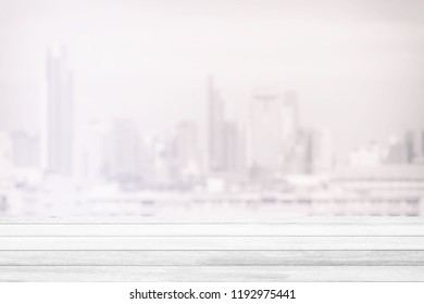 White Wood Table with Blurred White Cityscape Background, Suitable for Product Display and Business Concept.
