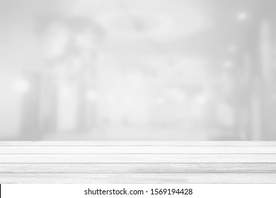 White Wood Table with Blurred White Restaurant Room Background, Suitable for Product Display and Business Concept.