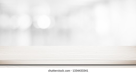 White wood table, tabletop, desk over blur store with white bokeh light background, Empty wood table, shelf, counter, desk for retail shop product display background, banner, mockup, template