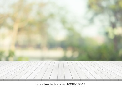 White wood table top on green blurred background,space for montage product