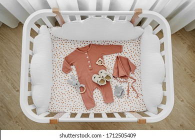 White wooden baby crib with pillows shaped clouds  in baby's room. Newborn clothes and accessories in cot. Top view of child's bed