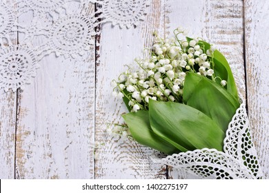 white wooden background with a bunch of lily of the valley flowers lying in the corner