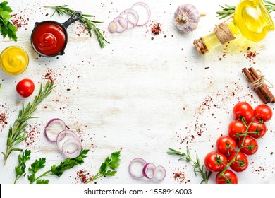 White wooden background of cooking. Spices and vegetables. Top view. Free space for your text.