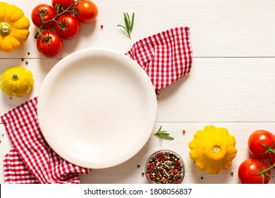 White wooden background with empty plate and ingredients, tomatoes and rosemary, pattypan squash and spices , top view