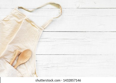 White wooden background with light linen apron, kitchen composition, copy space
