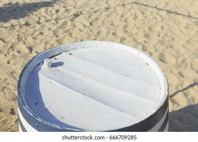 White wooden barrel table by the sea in Greece, Empty barrel for product display, Defocused beach in the background