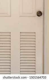 White wooden bathroom door with louver on concrete wall.
