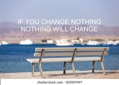 "White wooden bench on sunny seafront at sea bay, in front of beautiful scenery with mountains and white boats. Motivational text ""If you change nothing nothing will change"""