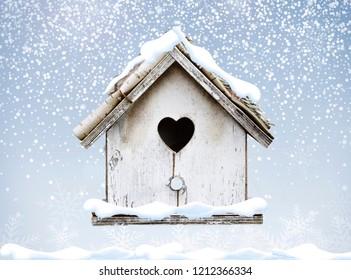 White wooden bird house winter snow falling down on bark roof heart shape