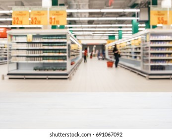 White wooden board empty table in front of blurred background. Perspective table over blur in supermarket - can be used for display or montage your products. Mockup for display of product.