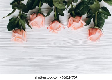 A white wooden board with pink roses.