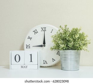 White wooden calendar with black 1 may word with clock and plant on white wood desk and cream wallpaper textured background , selective focus at the calendar