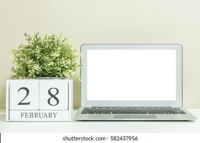 White wooden calendar with black 28 february word with white blank space at center of computer notebook on white wood desk and cream wallpaper textured background in selective focus at the calendar