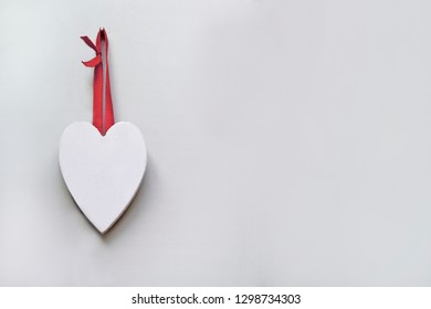 White Wooden Carved Heart Hanging by a Ribbon on a Wall for Valentines Day