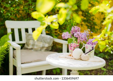 White wooden chair table with a bouquet of lilacs spring garden. needlework, knitting Recreation area shade of trees own garden. Relax in nature. Clean air, peace for creativity and inspiration.