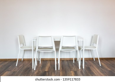 white wooden chairs with a table against the background of a white wall in the interior