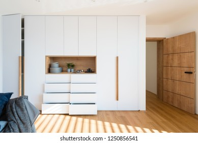 White wooden closet with open shelves in bedroom of modern house