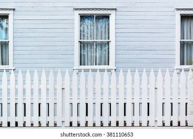 White wooden country style fence with windows of house at behind