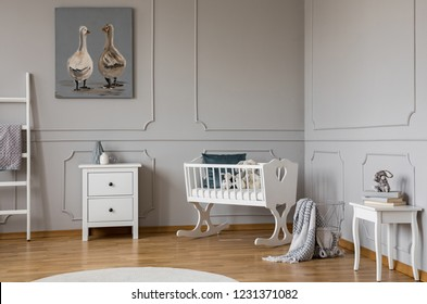 White wooden cradle with emerald pillow and toys in the corner of stylish scandinavian baby bedroom interior, real photo with copy space on the empty wall
