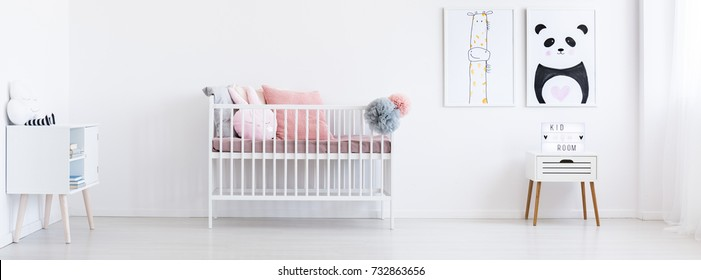 White wooden crib with cute pillows and tulle pompoms in the room with two posters with panda and giraffe