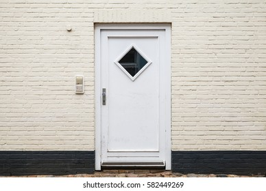 White wooden door in brick wall, European living house entrance