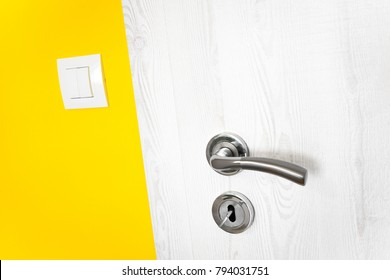 White wooden door with metal handle and keyhole with key in a vivid duck yellow wall in a modern house with a small electricity light switch in a close up diagonal view