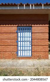 white wooden door protected by blue metal grid door in a red brick wall