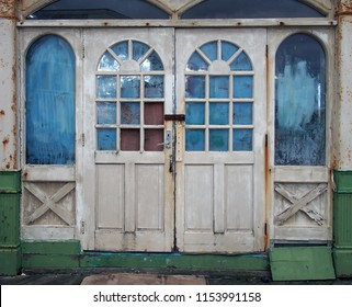 white wooden doors in an abandoned derelict house with broken and vandalized painted over windows
