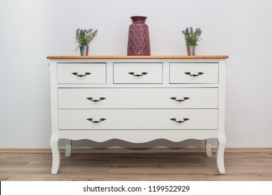 White wooden dresser with three vases and flowers on white wall background. Chest of drawers close up.