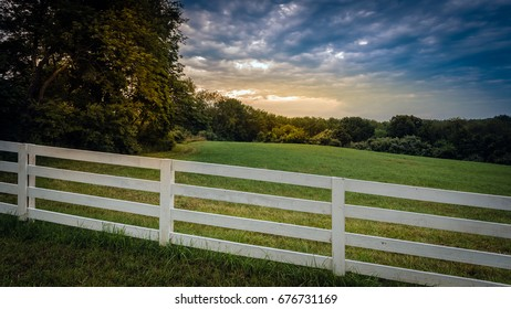 A white wooden fence along side a country meadow at sunrise