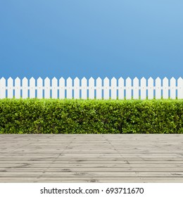 White wooden fence and wooden floor on a clear blue sky background. Green bush or Green leaves wall in the park