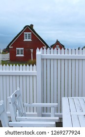 White wooden fence and white garden furniture in the foreground, idyllic thratched houses in the background, North Sea Island Fanoe, Denmark