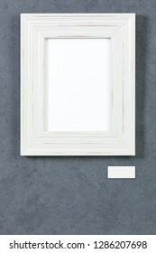 White wooden frame on grey painted wall, picture area isolated with clipping path. Blank caption tag and copy space below