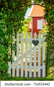 White wooden garden gate with heart and number plate (number removed). Red wooden cabin blurred in background, Hedgerows beside gate.