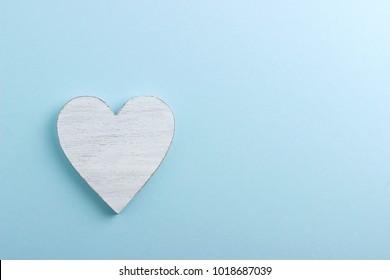 White wooden heart on blue cardboard background