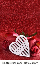 white wooden heart and two roses for valentines on red glitter background  with copy space for own text
