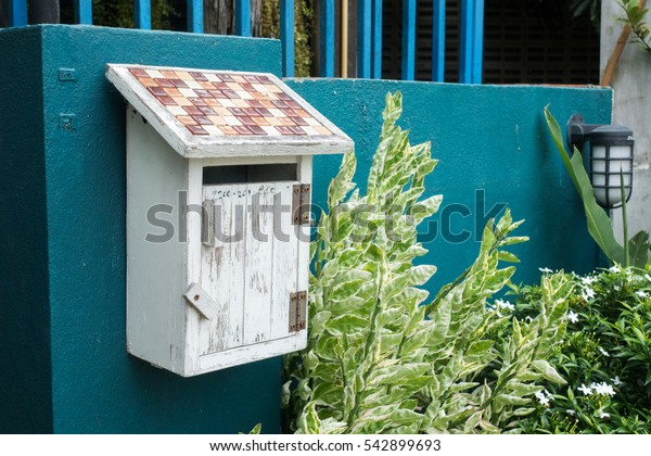 White wooden mailbox on green concrete wall