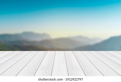 White wooden planks floor with blurred mountains and blue sky background.