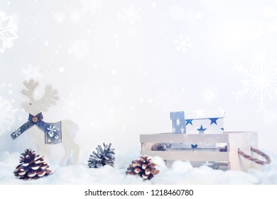 White wooden reindeer, cones in the snow and wooden container with presents from copy space with snowflakes