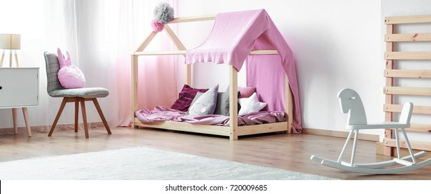 White wooden rocking horse standing next to a large carpet and a modern child's bed in a monochromatic kid bedroom