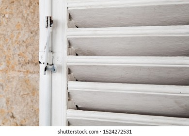 White wooden shutters with lock, close-up photo with selective soft focus