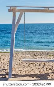 White wooden swing at the shore of Black Sea in Romania