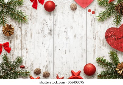 White wooden table with christmas tree and decorations top view. Free space for text. Christmas balls, bow, walnut, pine cone, stars and gift beside.