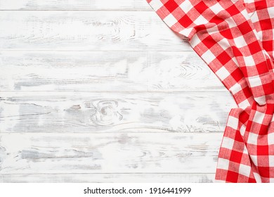White wooden table covered with red tablecloth. View from top. Empty tablecloth for product montage. Free space for your text
