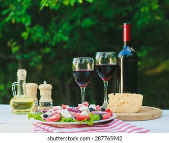 a white wooden table with Greek salad, olive oil, spices, a bottle of wine and two wine glasses on it