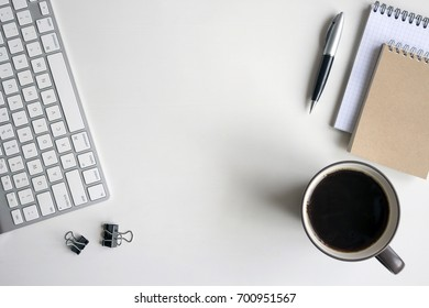 White wooden table with keyboard, pen, notebook, document clips and a cup of coffee. Workspace top view with copy space.