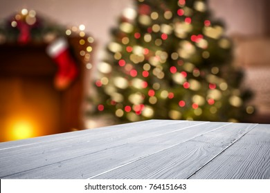 White wooden table of space for your decoration with background of fireplace and christmas tree.