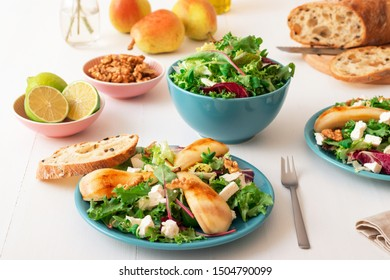 White wooden table with walnut salad, caramelised pears and feta cheese. Turquoise dishes with salad, slices of twisted swiss bread with olives, limets, bottle of olive oil and whole pears.